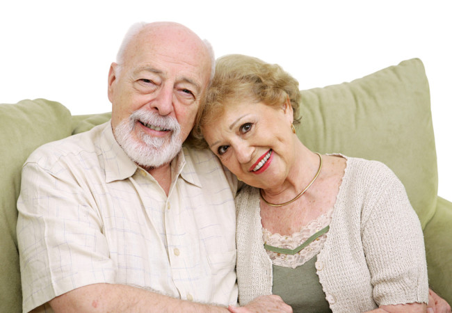 An attractive senior couple at home on the couch together. Isolated on white.